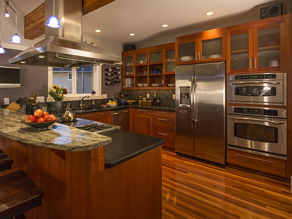 Contemporary upscale home kitchen interior with wood cabinets an